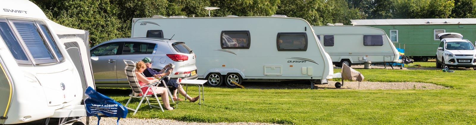couple relaxing next to their caravan in York Meadows