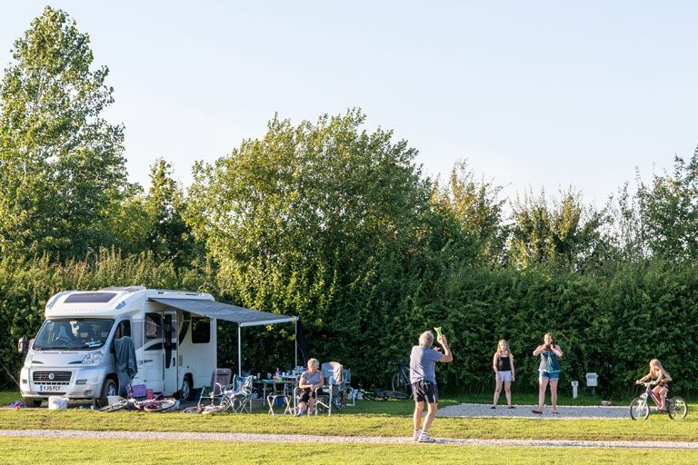 family playing games next to their motorhome pitch at York Meadows