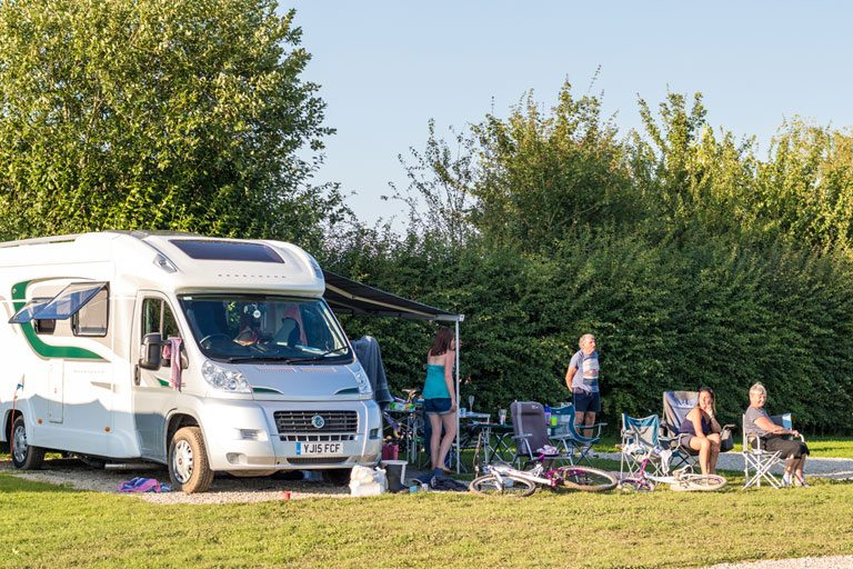 family relaxing next to their motorhome on a York Meadows hard standing pitch
